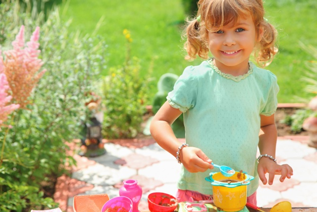 Smiling little girl plays cook in garden