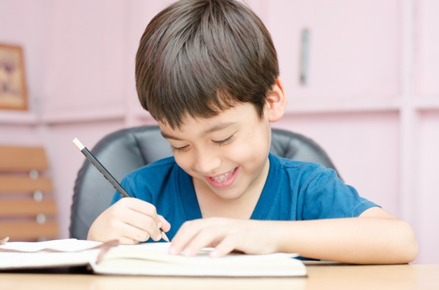 Little boy writing homework in the room with smiling