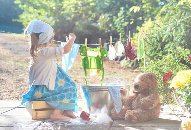 Barefoot girl washing her toys clothes near washtub