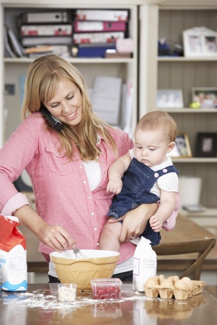 Mother And Baby Daughter Preparing Ingredients To Bake Cakes In Kitchen